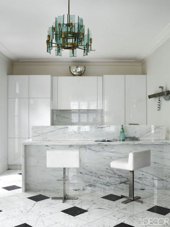 a refined minimalist kitchen with sleek cabinetry, an integrated hood, a white stone kitchen island, white stools and a green chandelier