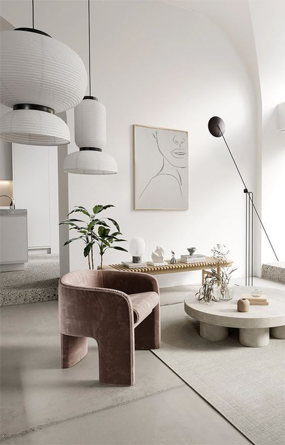 a refined minimalist living room done in pure neutrals and accented with a lovely mauve velvet chair that adds a soft touch