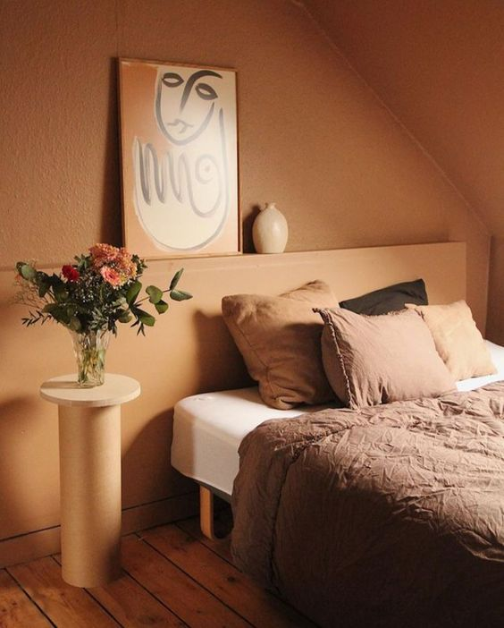 17 a warm earthy tone bedroom with a lovely wall color, comfy furniture and an artwork plus a bit of cool pillows