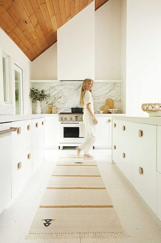 a serene white kitchen with cool cabinetry, wooden knobs and a matching white hood that doesn't differ form them at all