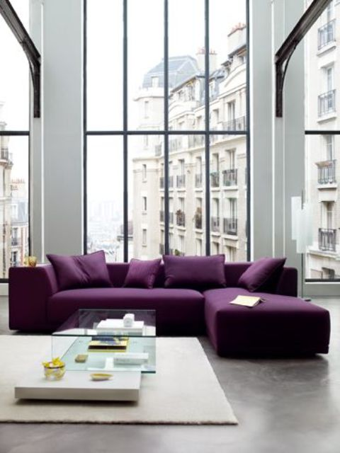 a contemporary living room done in neutrals, with double height windows, a purple sectional, a glass table and a neutral rug