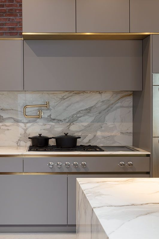 a sleek minimalist grey kitchen with chic cabinetry, gold touches and an integrated hood that looks like a cabinet
