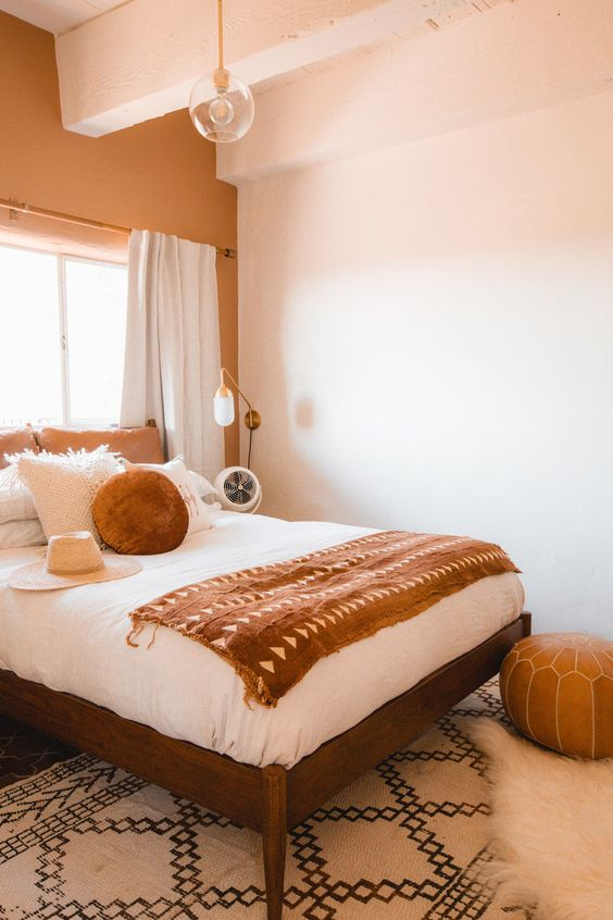 19 a small and cozy bedroom done in earthy tones, with rust and brown shades, a comfy bed, a leather pouf and cool bulbs