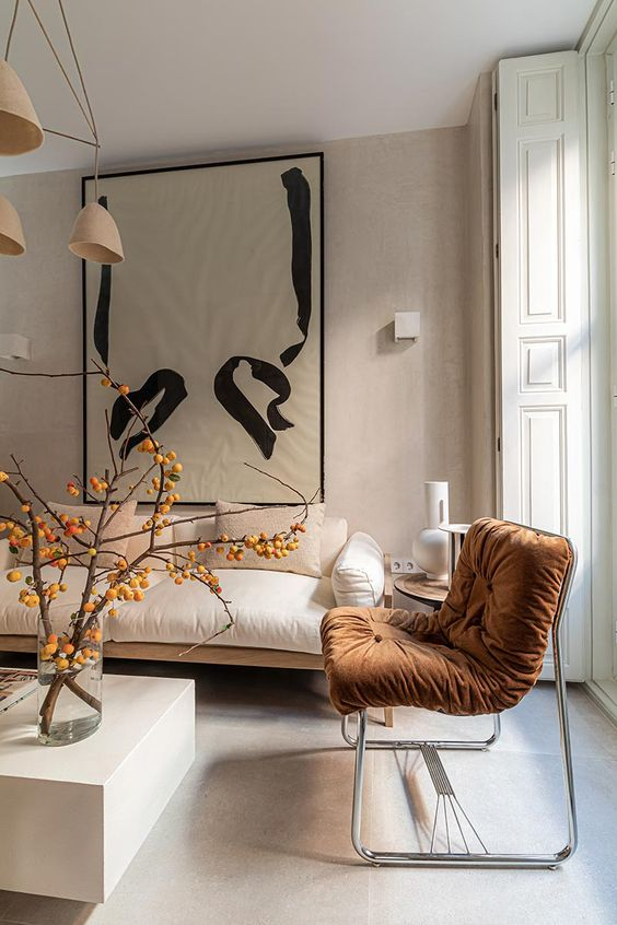 an adorable minimalist living room done in neutrals, with a terracotta upholstered chair, branches in a vase and tan chandelier