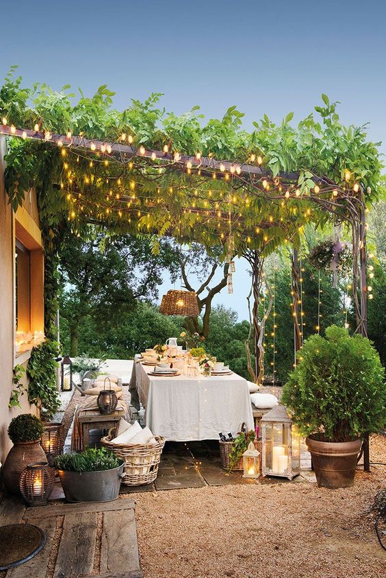 an outdoor dining zone with wooden furniture, baskets, potted greenery, candle lanterns and lights creatign a canopy over the space