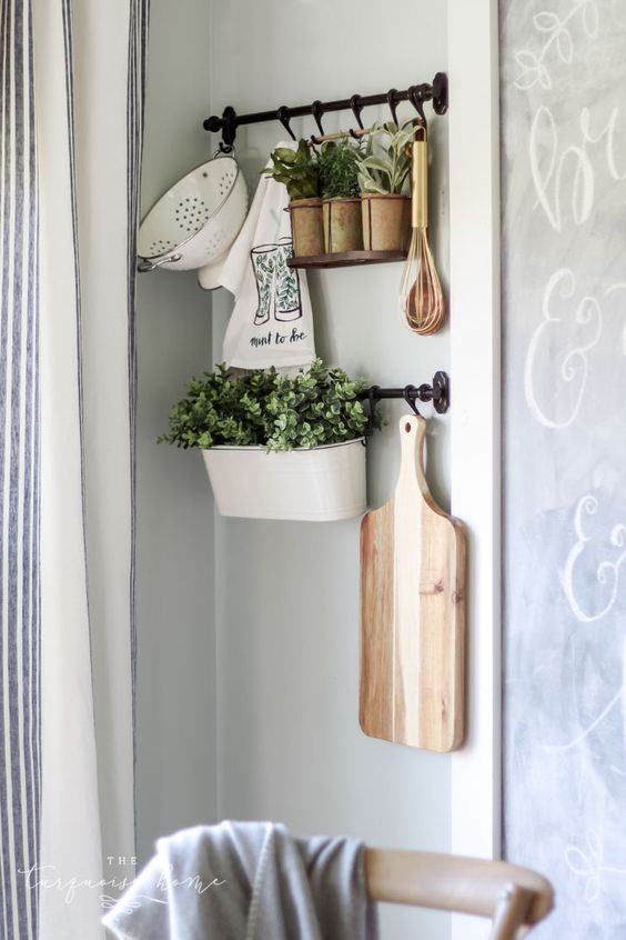 rustic kitchen wall decor with railings, potted greenery, a cutting board, some vintage kitchen stuff is chic