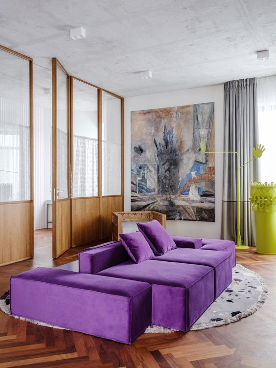 a contemporary living room with a neutral base, a bold purple sofa, a statement artwork, grey curtains and a neon yellow table