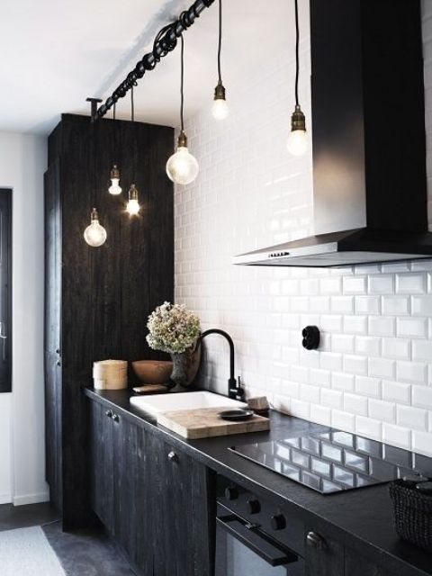 20 a modern Scandinavian black and white kitchen with a white subway tile backsplash and black cabinetry and cool bulbs