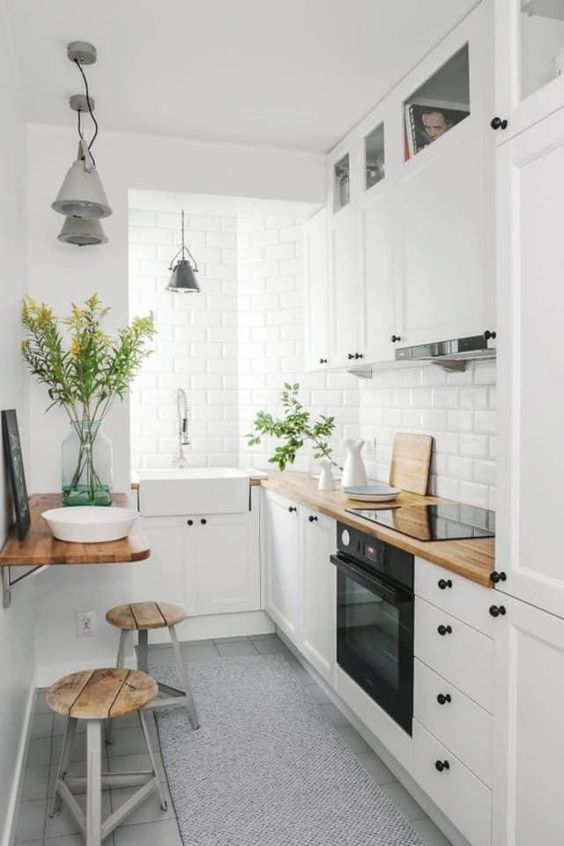 a small and cozy white kitchen with an incorporated hood, butcherblock coutnertops and built-in appliances plus a small meal zone