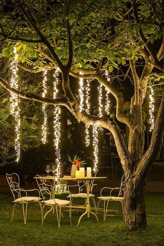an outdoor dining space with refined metal furniture, candles on the table and hanging lights over the space