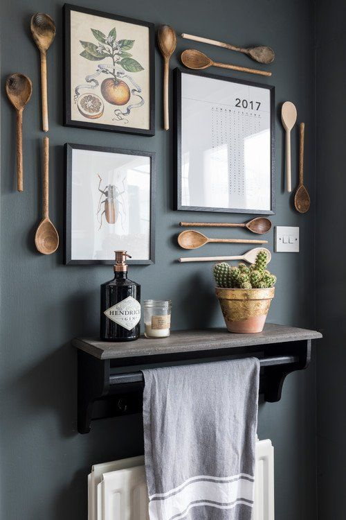 lovely kitchen wall decor with wooden cutlery, vintage posters and a calendar, a potted cactus and a candle