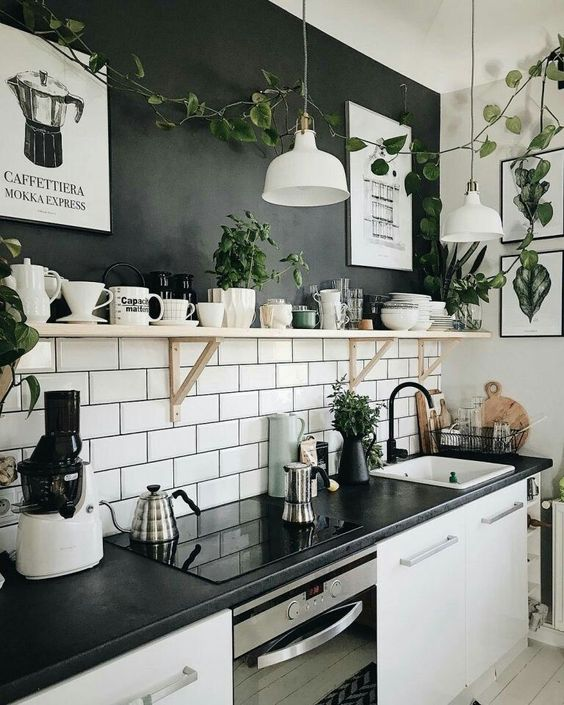 a chic kitchen design in black and white, with a black and white subway tile accent wall, white cabinetry and black countertops