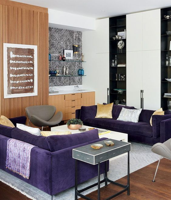 a contemporary living room with two purple sofas, grey chairs, light stained and black and white storage furniture