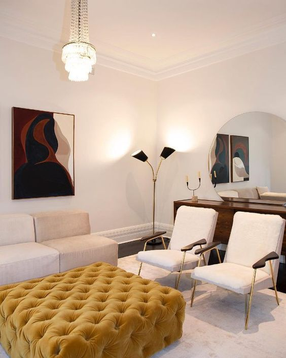 a fantastic minimalist living room done in neutrals, with a sunny yellow tufted ottoman and a bold artwork for a touch of color