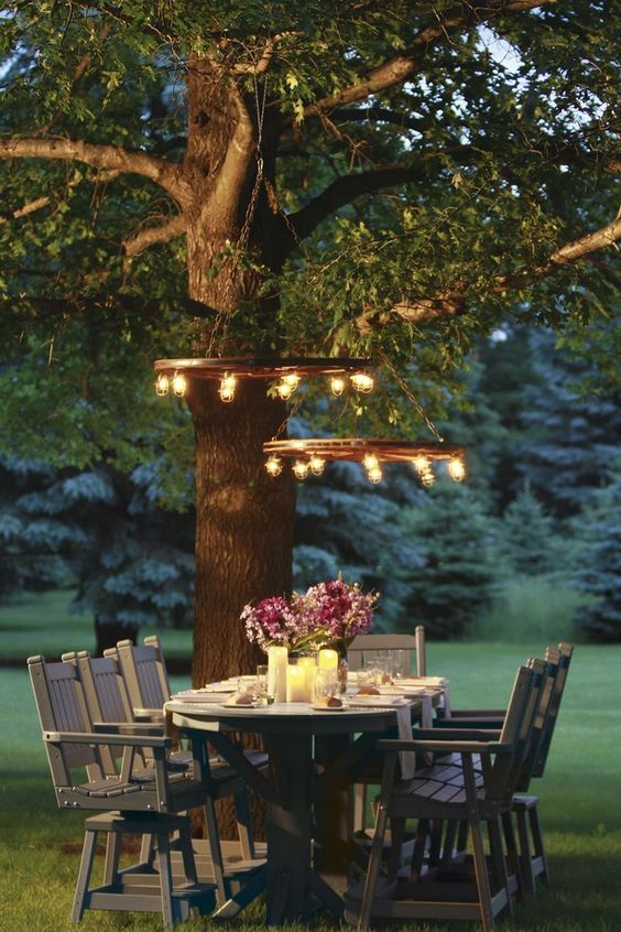an outdoor dining area with rustic wooden furniture, candles on the table and rustic bulb chandeliers is amazing