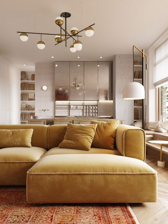 a beautiful minimalist space with silver kitchen cabinets and a mustard yellow sectional plus brass touches for elegance