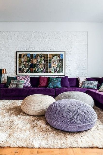a cool living room done in neutrals, with a large purple sectional, a bold artwork, colorful pillows and a trio of poufs