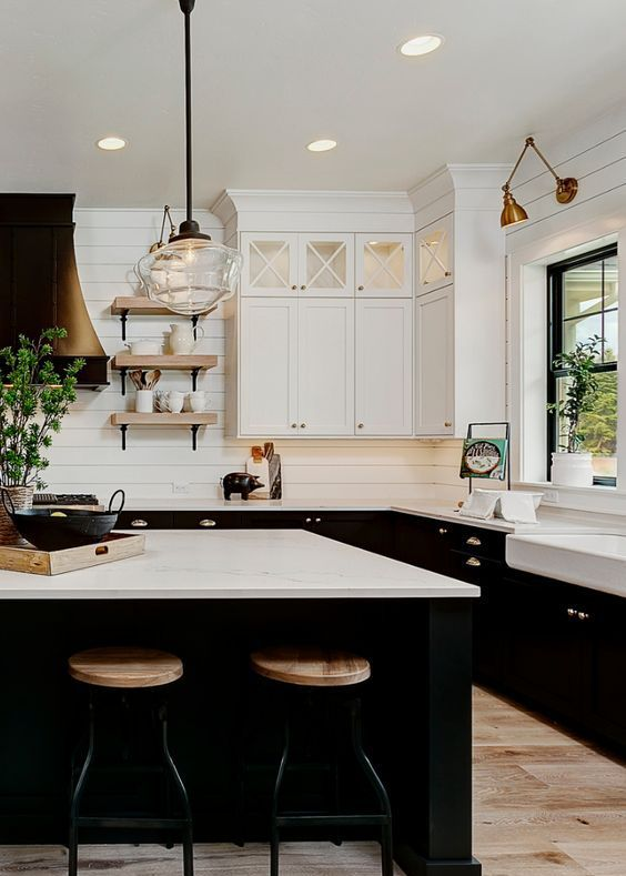 22 a stylish black and white farmhouse kitchen withwhite beadboard walls, black cabinetry, a metal hood and touches of blonde wood