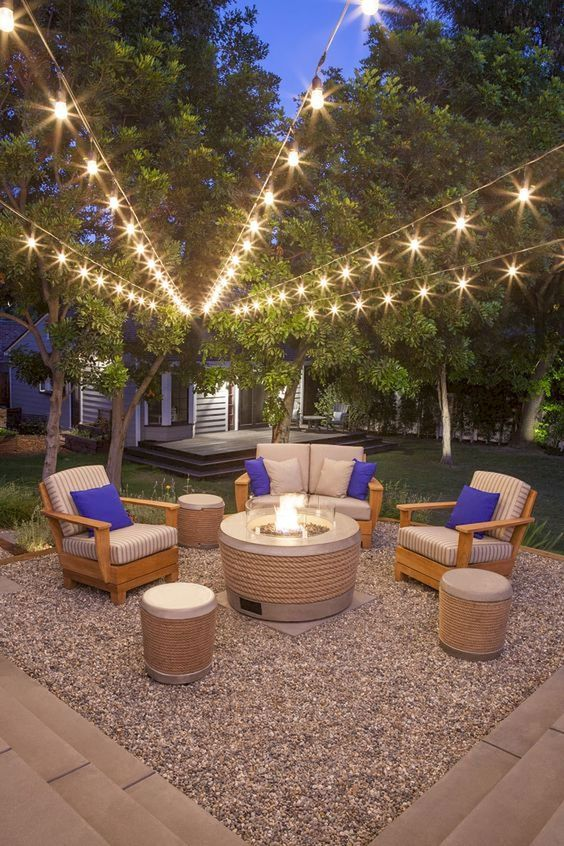 a stylish modern outdoor living room with a modern fire pit and string lights over the space is welcoming and chic