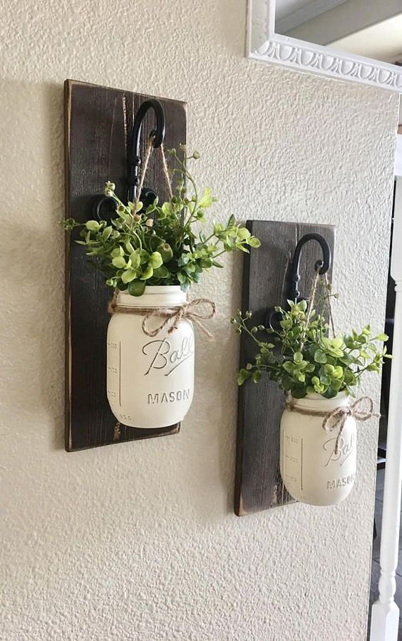 dark stained wooden plaques with hooks and whitewashed mason jars with greenery for lovely farmhouse wall decor