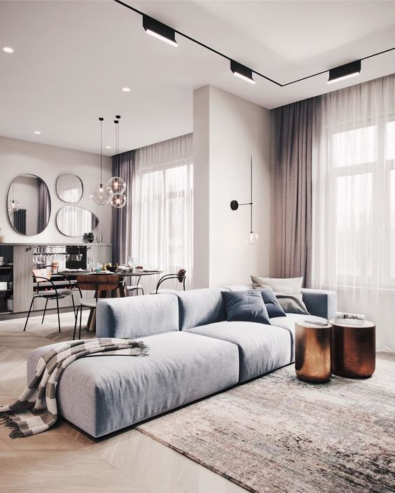 a catchy minimalist interior done in the shades of grey and with a light blue sofa and copper side tables