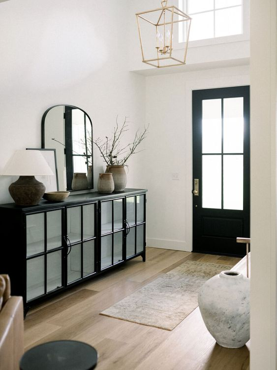23 a refined entryway in black and white, with a black storage unit, a curved mirror, a rug, a bench, a black door and a pendant lamp
