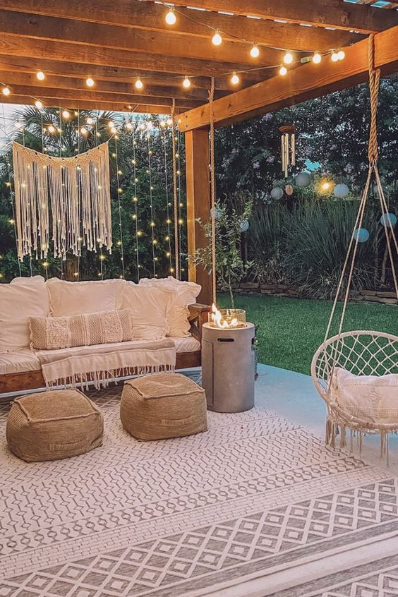 a welcoming backyard patio with boho furniture, neutral textiles, string lights and macrame over the space