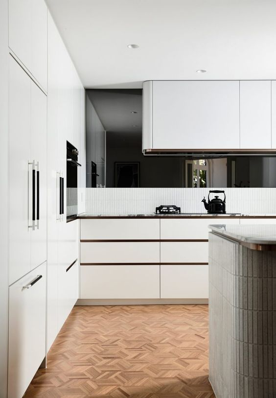 a white contemporary kitchen with sleek cabinets and a curved hood over the cooker is a stylsih idea