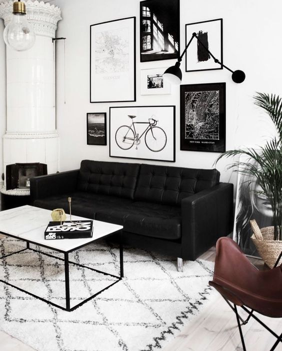 a Scandinavian living room with a black leather sofa, a leather chair, a low coffee table and a black and white gallery wall