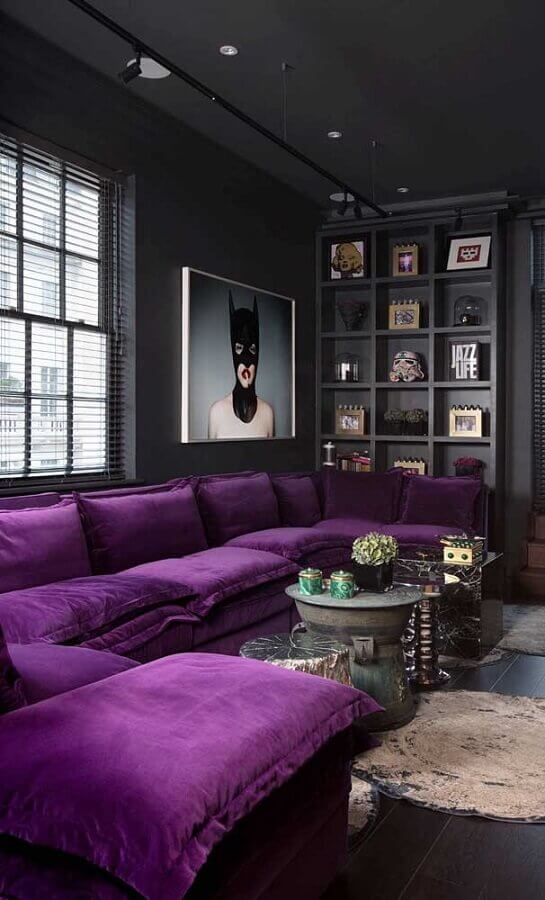 a moody contemporary living room done in black and graphite grey, a built-in shelf for displaying, a purple sectional and a statement artwork