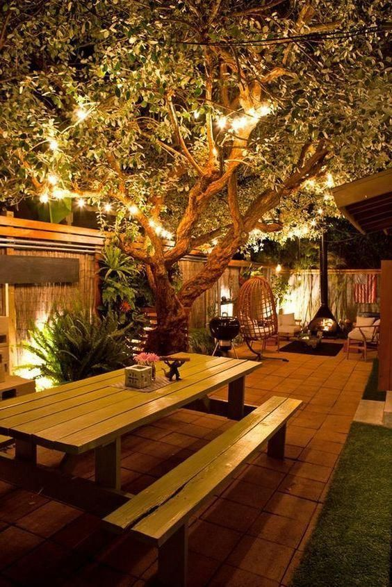 a stylish and cozy backyard with strign lights on the branches and built-in lights looks very welcoming