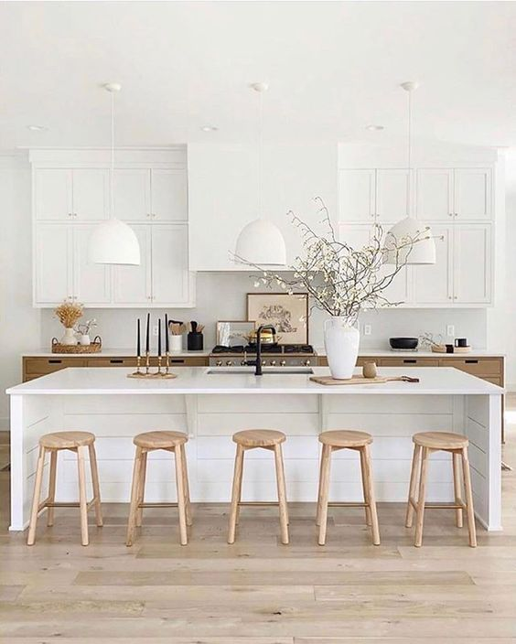 an elegant white farmhouse kitchen with a hood that matches the upper cabinets, white stone countertops and pendant lamps