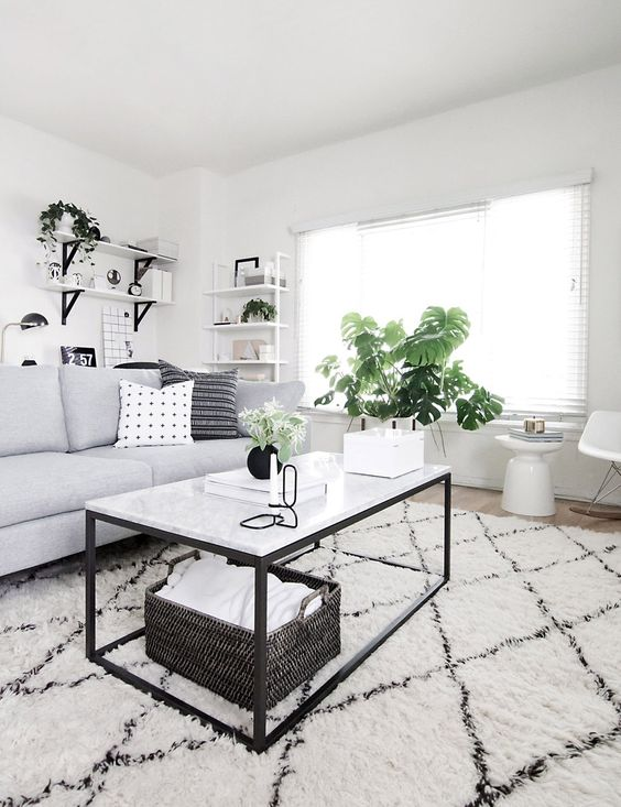 a Scandinavian living room with a grey sofa, black and white furniture, potted plants, a black basket and a printed rug