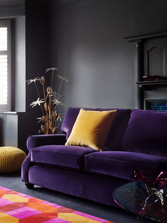a moody living room in dark greys spruced up with a deep purple sofa, yellow pillows and a colorful geometric rug