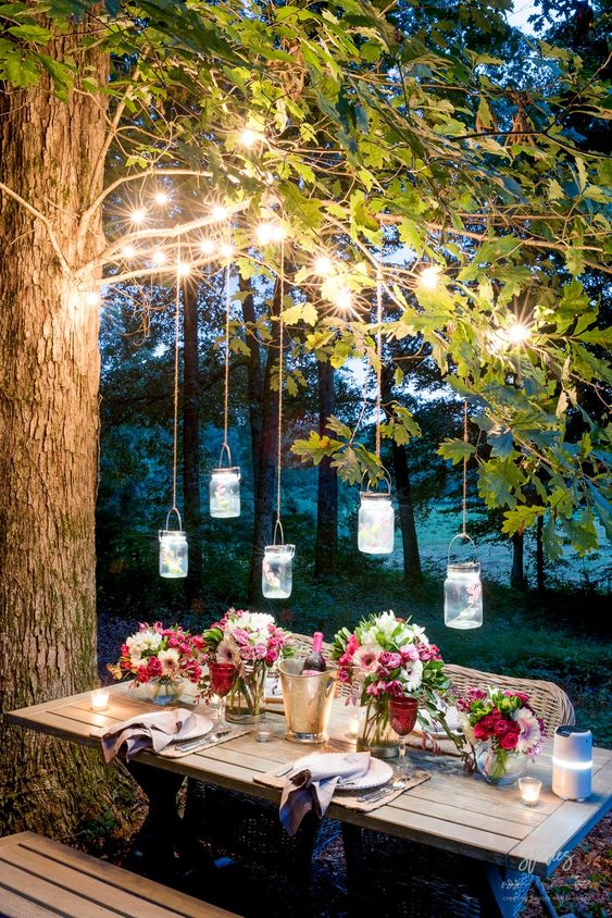 string lights on the branches and pendant jar lanterns over the table plus candles on the table is very welcoming