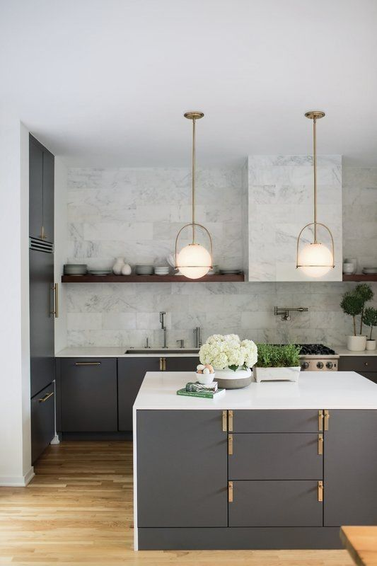 a chic modern kitchen with grey cabinetry, gold touches, white countertops, white marble tiles on the backsplash and a hood plus pendant lamps