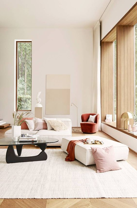 a minimalist neutral living room done with chic furniture, a terracotta chair, blankets and pillows for a touch of color