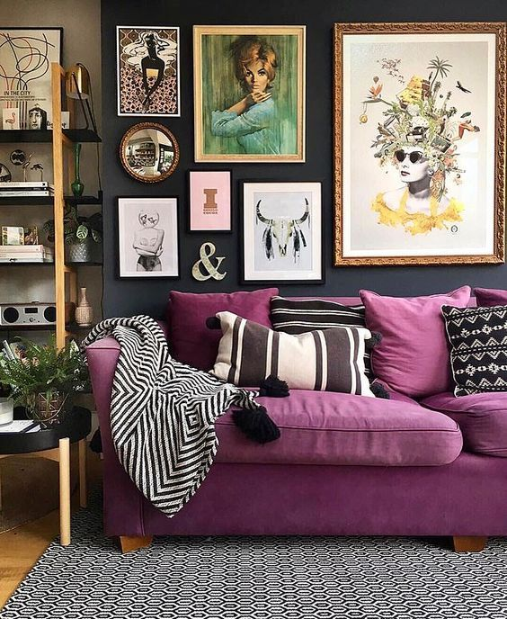 a moody living room with a purple sofa, an open shelving unit and a bright gallery wall plus printed pillows is cool