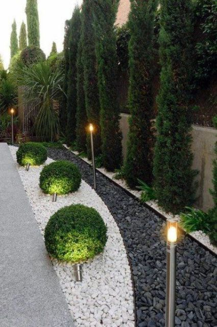 an elegant backyard or garden space with outdoor lamps all along it is a stylish and very refined space