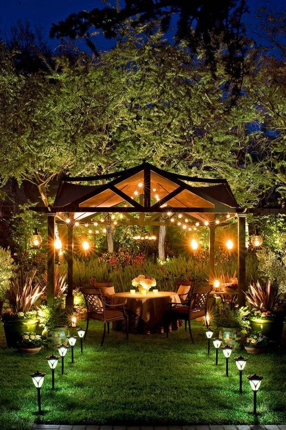 a backyard dining zone with lights over the space and outdoor lamp lining up the path looks very welcoming