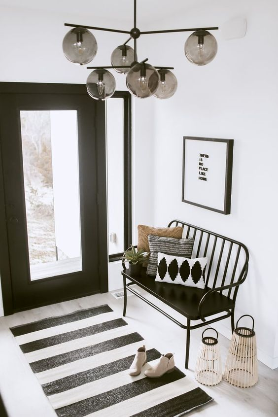27 a chic Scandinavian entryway with a black bench, a striped rug, candle lanterns, printed rugs and a catchy chandelier