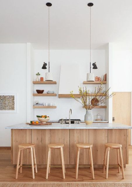 a contemporary white kitchen with light stained cabinetry, white stone countertops, floating shelves and a white hood plus pendant lamps