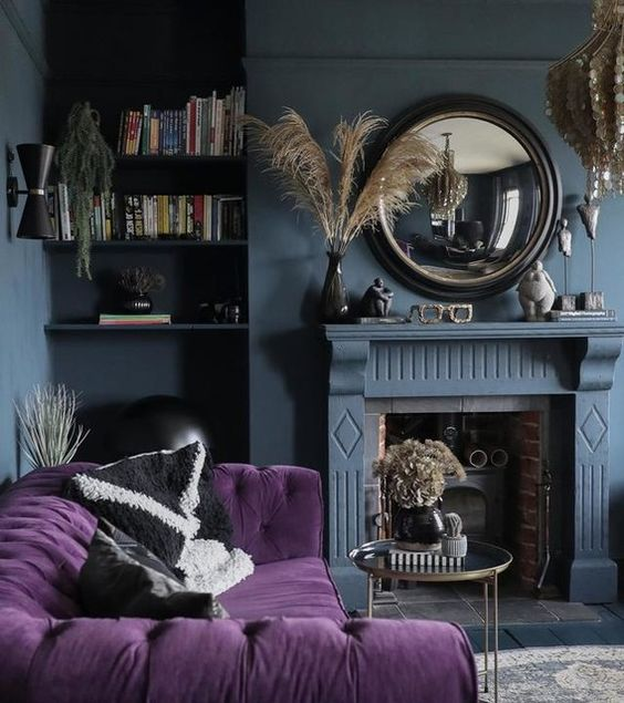 a moody living room with slate grey walls, a fireplace, a purple tufted sofa, a round mirror and a mother of pearl chandelier