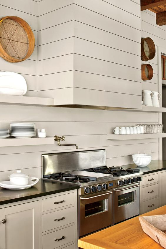 a creative modern kitchen done with ivory beadboards, black countertops, metal appliances and a seamless hood and shelves