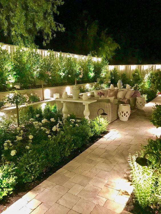 a lit up backyard with outdoor garden lamps all around, hidden and not, is a very welcoming garden space