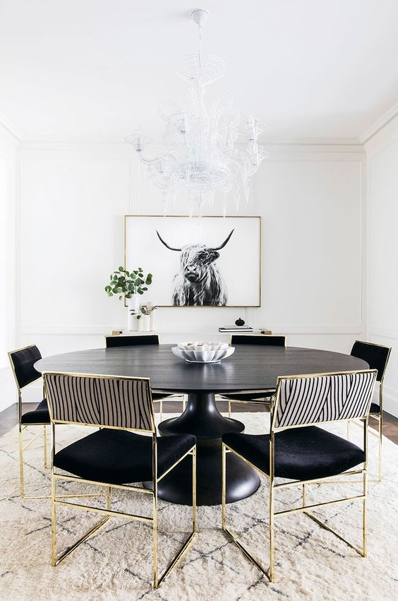 an elegant dining room with black furniture with gold frames, a printed rug and a statement chandelier and an artwork