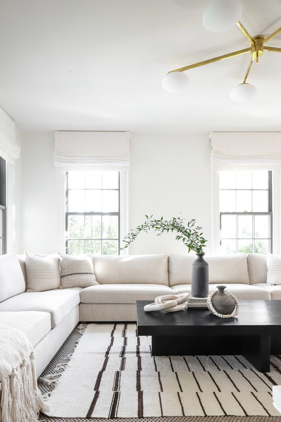 29 a modern black and white living room with a large sofa, a low black table, a vase with greenery and a chic chandelier