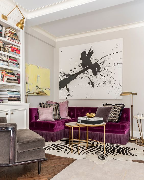 a refined and bold living room with a purple sectional as a centerpiece, a graphic artwork, a built-in bookcase and layered rugs