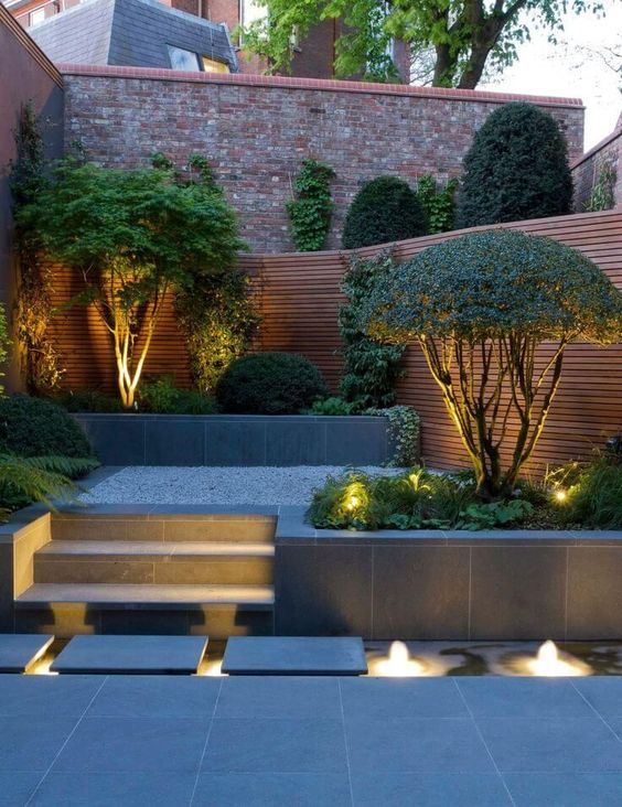a stylish minimalist backyard with built-in lights and lit up trees that are highlighted with these lights