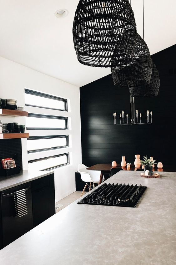 a bold kitchen with a black accent wall, black cabinetry and window frames plus black rattan pendant lamps